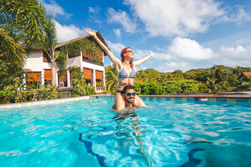 Young attractive couple having fun in the outdoor pool near villa, the girl sits on the shoulders of the guy, luxury vacation, real estate in the tropics, honeymoon