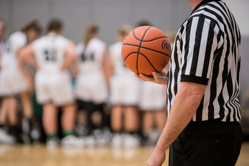 Referee holding basketball during timeout