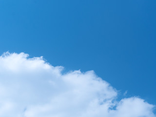 A background of the deep blue sky half covered with a patch of cloud