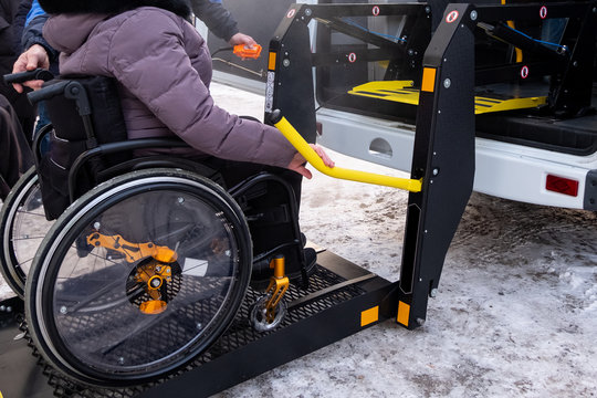 A man presses a button on the control panel to pick up a woman in a wheelchair in a taxi for the disabled. Black lift specialized vehicle for people with disabilities. Yellow handrail. Winter.