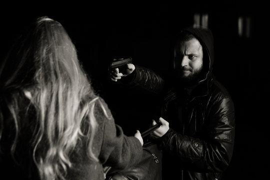 Night street robbery scene: man taking away young female bag