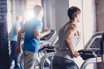 A group of young men doing jogging on a treadmill.
