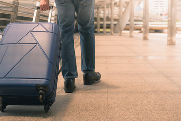 Traveler with a suitcase on the sidewalk,traveling bag on urban city  background, travel concept,copy space.