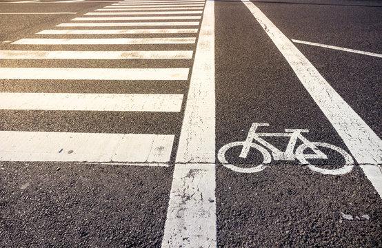 Bike lane symbol with crosswalk on asphalt street