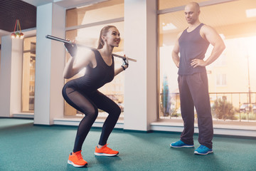 Girl doing squatting under the control of trainer