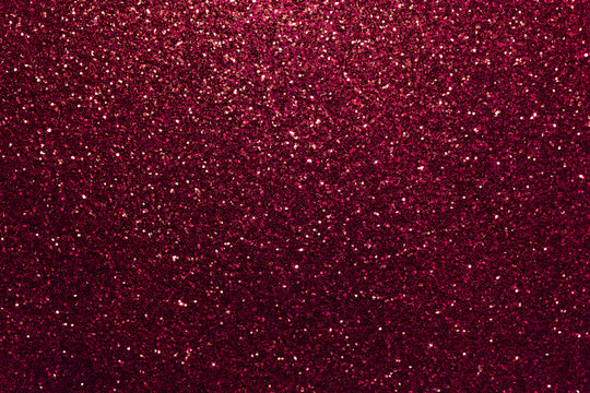 Dark red sparkling background from small sequins, closeup. Brilliant backdrop.