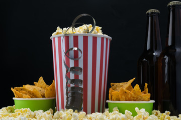 three paper cups of food and two bottles of beer for watching movies