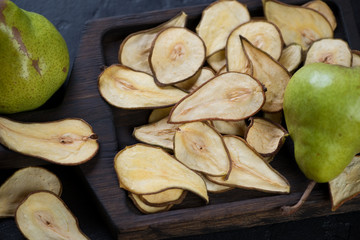 Close-up of crispy fruit chips made of pear on a wooden serving board, horizontal shot