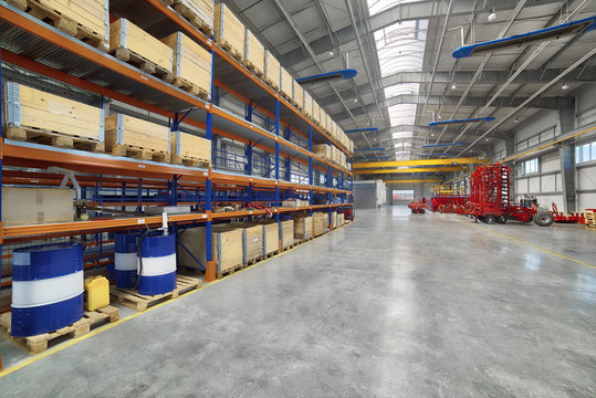 Factory assembly shop. High storage racks with wooden boxes