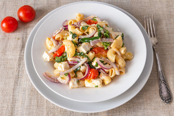 Warm pasta salad, cherry tomatoes, feta cheese and onions on a plate, top view, rustic background