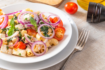 Warm pasta salad with cherry tomatoes, feta cheese and onions on a plate on the table