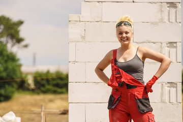 Woman in dungarees working on construction site