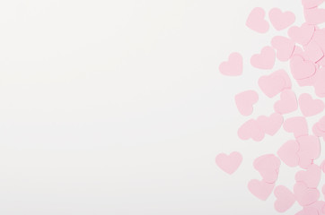 Small pink paper hearts on white background. Place for the inscription, congratulations on Valentine's Day, March 8. Copy space, top view, flat lay