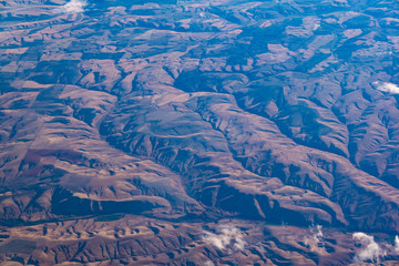 The view from the airplane  on  mountains.,Airplane wing out of window