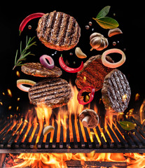 Beef milled meat on hamburger with vegetables and spices fly over the flaming grill barbecue fire.
