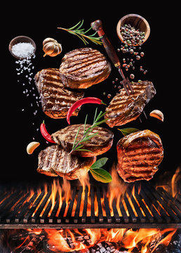 Grilled beef steaks with vegetables and spices fly over the glowing grill barbecue fire.
