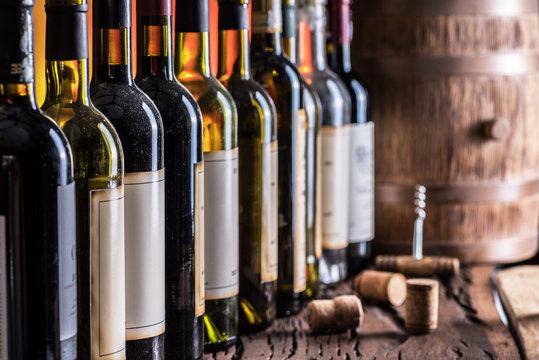 Wine bottles in row and oak wine keg.