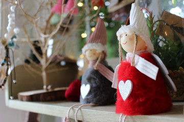 Cute Christmas angel doll with heart on her red dress on a shelf with other xmas decor in the background.