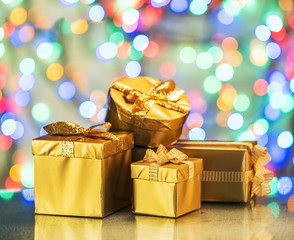 Golden gift boxes as a symbol of wishes and celebration. Colorful blurred bokeh background.