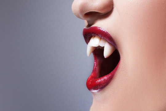 Sexy vampire. Women's lips with red lipstick. Screaming mouth with vampire fangs