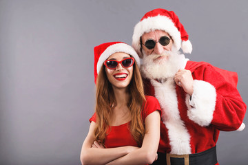Santa Claus with white beard wearing sungasses and young mrs. Claus wearing Santa hat, red dress and sunglasses standing and smiling on the gray background, New Year, Christmas, holidays, souvenirs