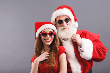 Santa Claus with white beard wearing sungasses and young mrs. Claus wearing Santa hat, red dress and sunglasses standing and laughing on the gray background, New Year, Christmas, holidays, souvenirs