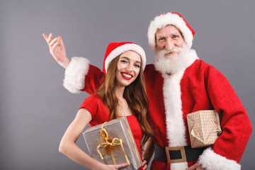 Santa Claus with white beard wearing sungasses and young mrs. Claus wearing Santa hat, red dress and sunglasses standing on the gray background and congratulates with Merry Christmass and Happy New