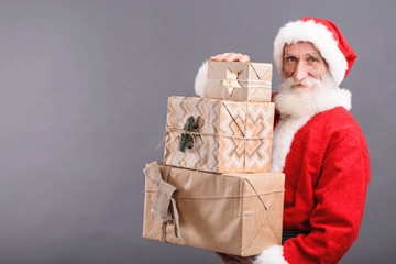 Santa Claus with a white beard wearing glasses and Santa outfit standing with a lot of gifts on the gray background, New Year, Christmas, holidays, souvenirs, gifts, shopping, discounts