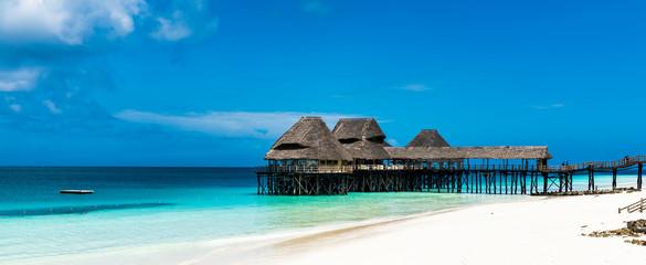 Papiers peints Zanzibar Beautiful Beach by the blue waters of the Indian ocean in Zanzibar. Zanzibar is an Island just off the coast of Tanzania - Africa.
