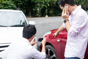 Male Driver take pictures of accident-damaged vehicle with a  holding  smartphone After Traffic Collision proof of insurance claim