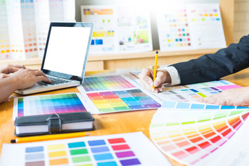 Professional Creative architect graphic desiner occupation choosing the Color pantone  palette samples for project on office desktop computer.