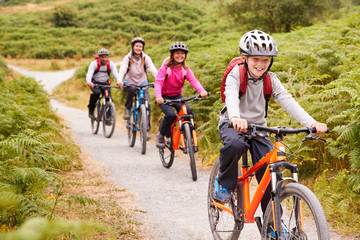 Pre-teen boy riding mountain bike with his sister and parents during a family camping trip, close up Fototapete