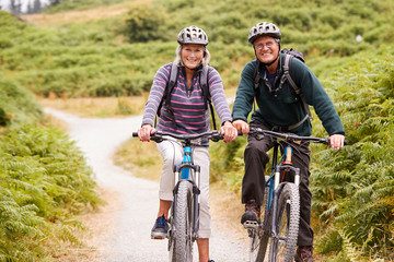 Senior couple sitting on mountain bikes in a country lane during a camping holiday, looking at camera, front view