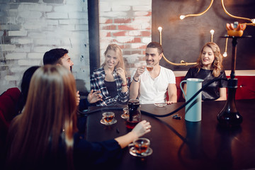 Group of friends drink tea and smoke hookah in bar with beautiful lamp on wall