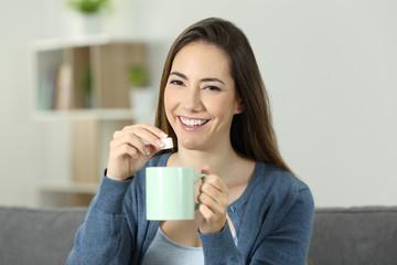 Happy woman throwing sugar into mug looking at you