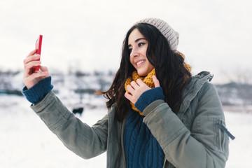 Beautiful brunette woman taking selfie in winter landscape