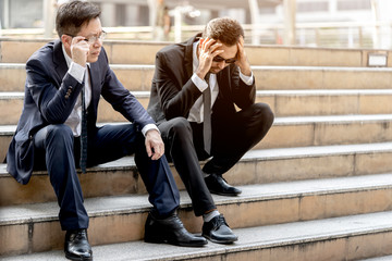 Two middle aged people unemployed businessman stress sitting on stair After experiencing problems despair low economic crisis, concept of Jobless Stressed business failure and unemployment problem.