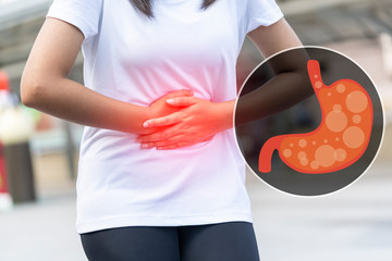Close up of body woman Suffering from stomach painful or Acid Reflux or Heartburn,Gas,Bloating,Belching and flatulence or gastrointestinal system disease. people,medical and health insurance concept