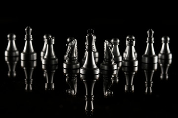 Chess pieces on black reflective background. High resolution image for sport and finance industry.