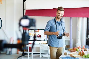 Portrait of handsome TV show host filming cooking program in studio , copy space