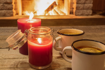 Cozy scene against fireplace with white enameled mugs with tea, and two candles.