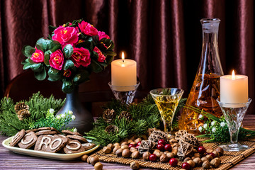 Christmas still life - flowers, candles, walnuts, hazelnuts, red currants, sweet biscuits and liqueur
