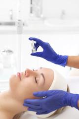 Witamina w ampułce kosmetycznej. Kosmetyczka nakłada na twarz kobiety preparat kosmetyczny