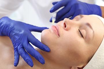Powiększanie ust. Pacjentka w klinice kosmetycznej, kosmetyczka wykonuje zabieg ostrzykiwania.