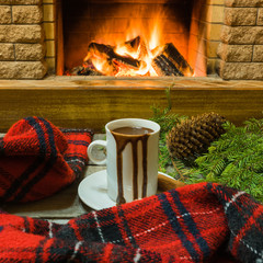 Cozy scene before fireplace with mug with hot chocolate, warm scarf and christmas decorations.