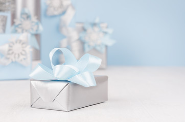 Festive silver metallic gift box with blue silk bow closeup and different elegance soft christmas presents on background in blur.