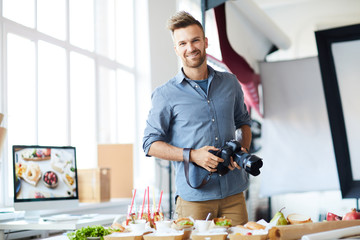 Waist up portrait of smiling photographer looking at camera while taking images of party table in studio, copy space