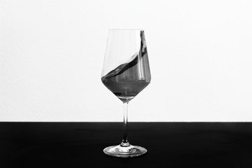 Black and white photo of red wine splashing out of a glass