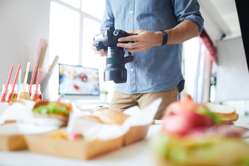 Mid section portrait of unrecognizable photographer holding camera with party table in foreground, copy space