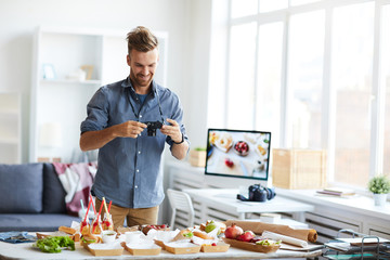 Waist up portrait of smiling photographer taking pictures of party table with food, copy space